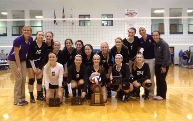 The volleyball team gathers for a team picture with the regional championship trophy after defeating Scott 3-2.