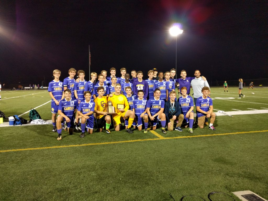 Boys soccer celebrates with their district trophy.